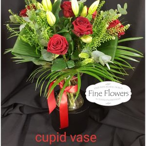 1/2 Dozen Red Roses with White Lilies. With a mix of foliages presented in a vase.