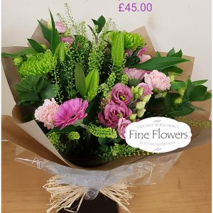 Handtied with Pink Gerbera, Carnations, Shamrock Blooms, Lisianthus and mixed foliages