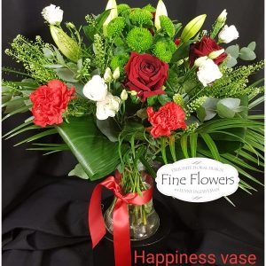 Mixed Handtied including 3 Red Roses, Lilies, Lisianthus, Santini and mixed foliages. Presented in vase.